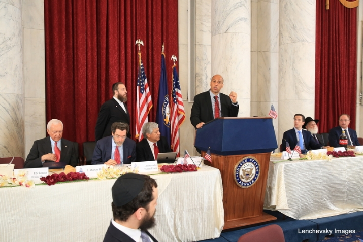 President pro tempore of the U.S. Senate Orrin Hatch, Ambassador Norm Eisen, Ezra Friedlander, Greg Rosenbaum, U.S. Senator Cory Booker (speaking), NYS Assemblymember Phil Goldfeder, Rabbi Hillel Zaltzman, Thomas Corby, , , ezra friedlander